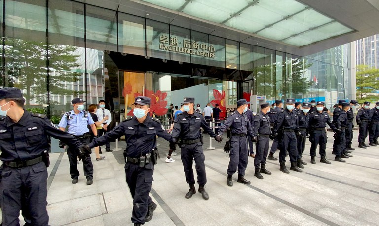 Security personnel form a human chain as they guard outside the Evergrande's headquarters, where people gathered to demand repayment of loans and financial products, in Shenzhen, Guangdong province, Sept. 13, 2021.  Credit: Reuters