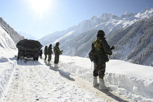 Indian army soldiers walk along a road near Zojila mountain pass that connects Srinagar to the union territory of Ladakh, bordering China Feb. 28, 2021. Credit: AFP