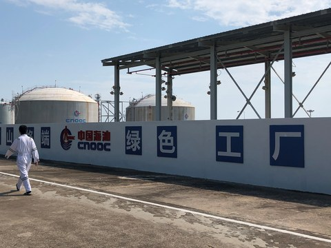 A worker walks past the logo of China National Offshore Oil Corporation (CNOOC) at its Nanshan liquefied natural gas (LNG) terminal in Hainan province, China September 24, 2019.