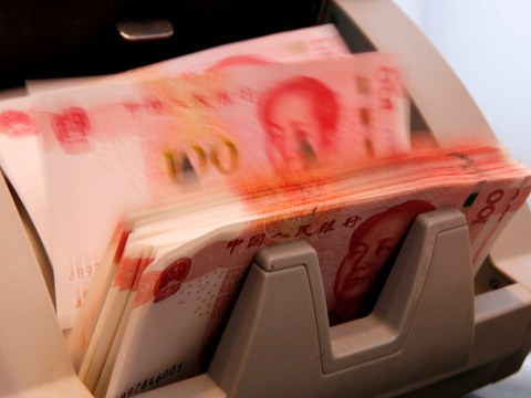 In a file photo Chinese 100 yuan banknotes are seen in a counting machine while a clerk counts them at a branch of a commercial bank in Beijing, China.