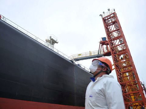 A dock worker wearing a face mask to prevent the spread of the coronavirus disease (COVID-19) looks at an oil tanker unloading crude oil at a port in Qingdao, Shandong province, China March 26, 2020.