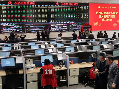 People attend a ceremony marking the opening of iron ore futures to foreign investors, at Dalian Commodity Exchange in Dalian, Liaoning province, China May 4, 2018.