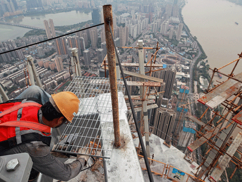 A construction employee works on the upper floors at the buidling site of the Wuhan  Greenland Center skyscraper in Wuhan, capital of central China's Hubei province, Sept. 28, 2020.