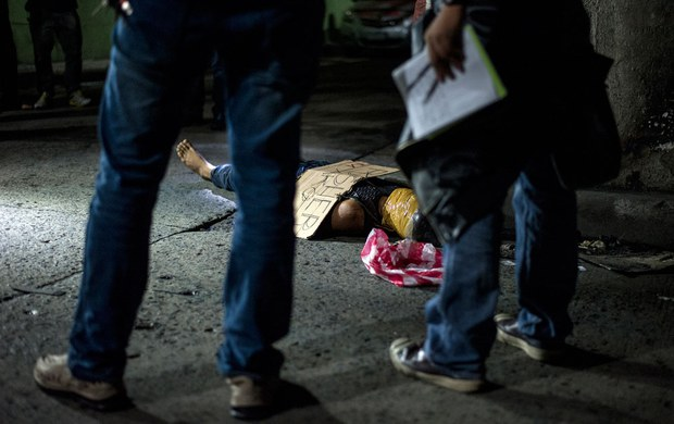 """Police officers investigate the body of an alleged drug dealer, his face covered with packing tape and a placard reading """"I'm a pusher,"""" on a street in Manila, the Philippines, July 8, 2016."""