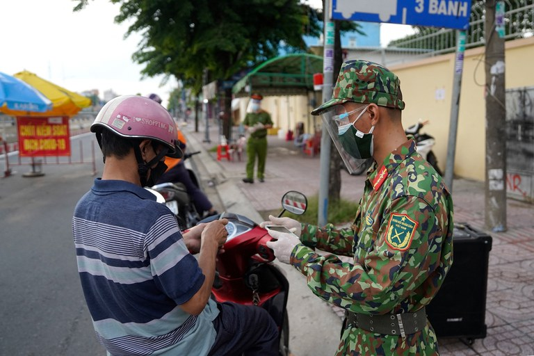 A Vietnamese military personnel (R) checks the travel documents of a motorist at a checkpoint in Ho Chi Minh City, Aug.  23, 2021,  Credit: AFP