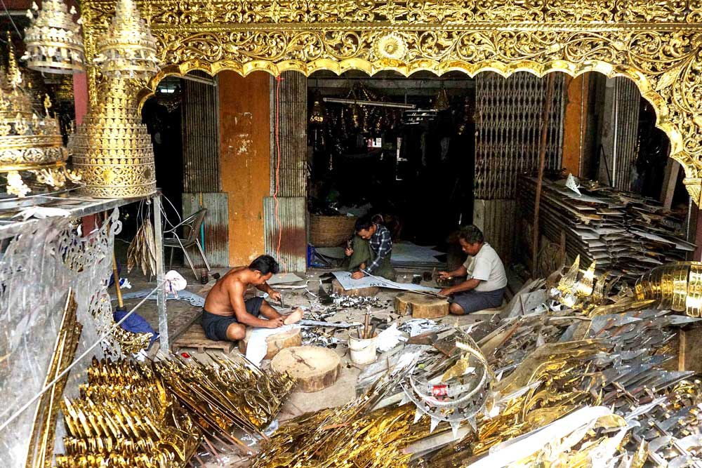 Craftsmen ply their trade at a casting workshop in Kyimyindaing, Yangon Region. Bronze handicrafts such as Buddha images, finials, crowning ornaments, bells, gongs and other figures are most often used in pagodas and temples. (Myo Min Soe/RFA)
