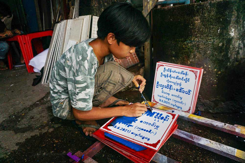 A young worker removes unwanted paint from a marble plate engraved with the names of donors and a dedication. (Myo Min Soe/RFA)