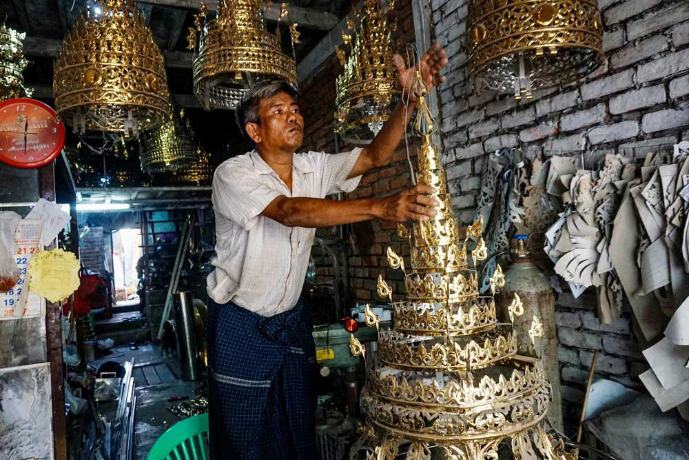A worker puts the final touches on a small holy umbrella for a pagoda's finial, which can take from one to two weeks to make, depending on the size. (Myo Min Soe/RFA)