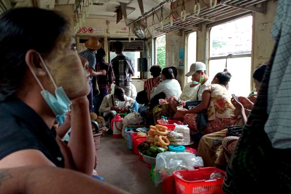 Metro rail commuters ride the Yangon train. During the morning run, most passengers kept their heads down as armed security personnel patrolled the carriages. (Myo Min Soe/RFA)