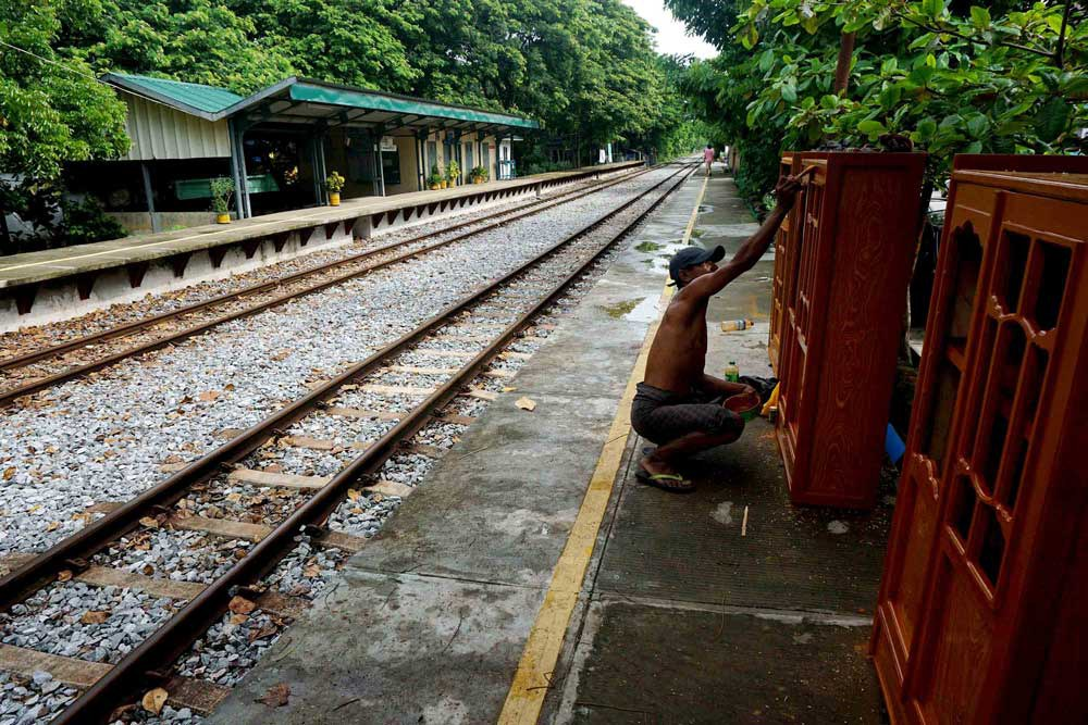 A furniture worker puts some touches on a cabinet at a station in suburban Yangon. With few railway workers on the job, there was no one to tell him he couldn't work there. (Myo Min Soe/RFA)