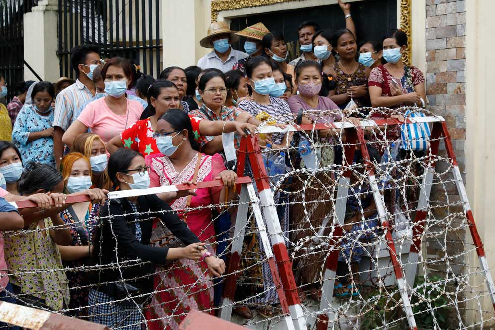 Friends and family members wait, hoping for the release of their loved ones Wednesday in Yangon. Myanmar's government began releasing about 2,300 prisoners, including activists and reporters. (Citizen journalist)