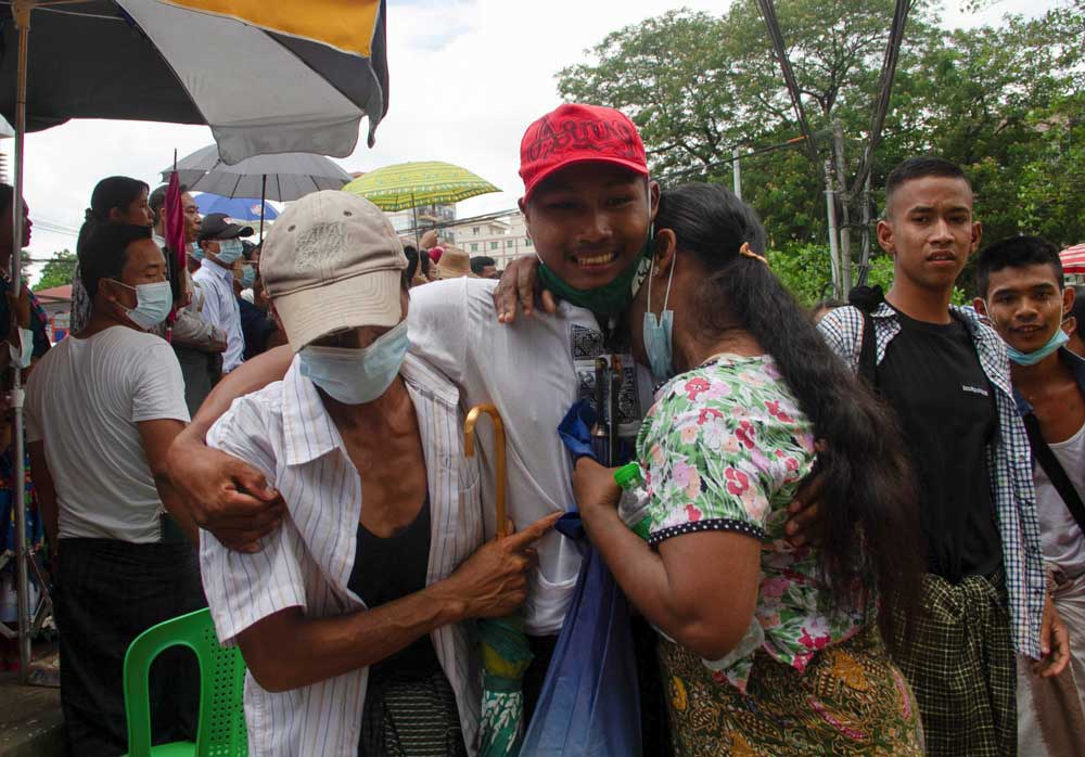 A released prisoner reacts with his relatives outside the Insein Prison. (Reuters)