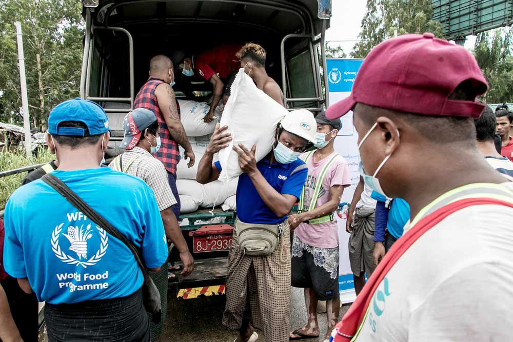 People receive bags of rice from the World Food Program on May 21, 2021 as part of efforts to supply food to residents of poor communities on the outskirts of Yangon. (AFP)