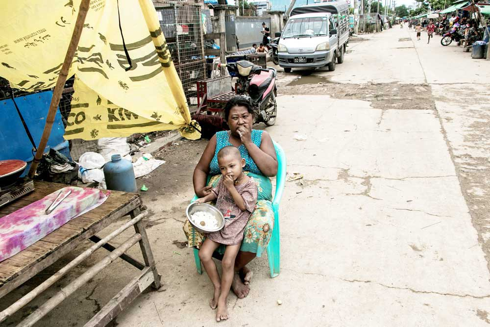 A mother and child eat in front of their home on the outskirts of Yangon. (AFP)