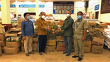 Oum Reatrey (2nd from L), governor of northwestern Cambodia's Banteay Meanchey province, receives some of the 10 tons of longans purchased by the central government to distribute to officials in his province, in Battambang, Aug. 30, 2021.