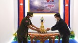 Cambodia's Minister Energy and Mines Suy Sem hands over the first drop of oil extracted from an offshore petroleum deposit to Minister of Defense Tea, Banh during a ceremony in Phnom Penh, Cambodia, June 9, 2021.