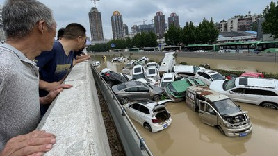 People look out at cars sitting in floodwaters after heavy rains hit the city of Zhengzhou in China's central Henan province on July 21, 2021.