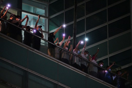 Employees of the Apple Daily newspaper shine phone torches from an office balcony and shout thanks to supporters down on the street below in Hong Kong, June 23, 2021. Credit: AFP