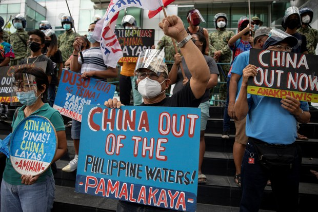 Activists stage a protest outside the Chinese Consulate, guarded by Philippine police, on the fifth anniversary of an international arbitral court ruling invalidating Beijing's historical claims over the waters of the South China Sea, in Makati City, Philippines, July 12, 2021.