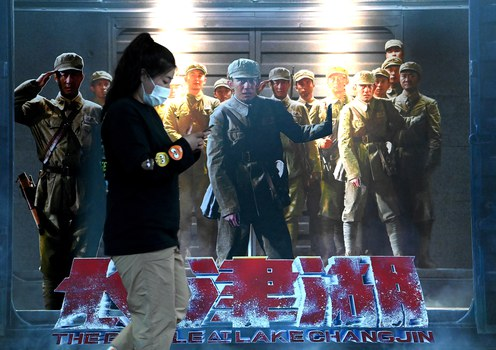 """A woman walks past a movie promotion poster for """"The Battle at Lake Changjin"""" at a mall in Beijing, Oct. 11, 2021."""