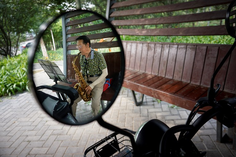 An elderly man is reflected in a rearview mirror of a electric tricycle as he plays a saxophone in a booth for people to rest along a road in Beijing, Aug. 22, 2021. Credit: AFP