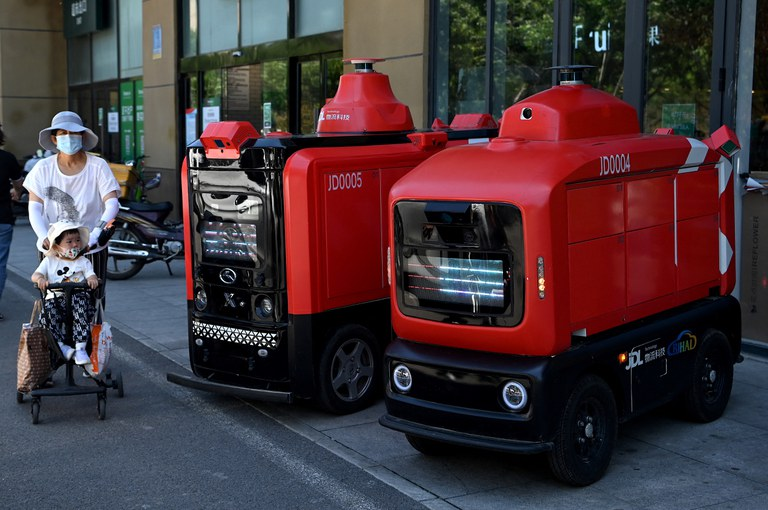People walk past Chinese e-commerce giant JD.com's autonomous vehicles used to deliver goods to customers, outside a supermarket in Beijing, June 18, 2021. Credit: AFP