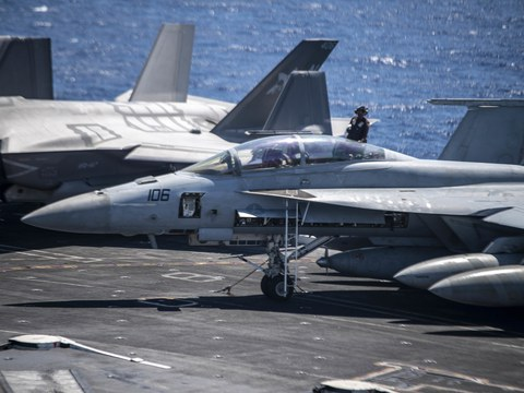 A U.S. sailor cleans an F/A-18F Super Hornet fighter jet on the flight deck of the aircraft carrier USS Carl Vinson (CVN 70) on Sept. 11, 2021, during deployment in the South China Sea.