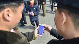 North Koreans read reports about the country's leader Kim Jong Un's arrival in Vietnam for his second summit with the U.S. President Donald Trump by using a smartphone in Pyongyang, North Korea, in this photo released by Kyodo February 27, 2019.