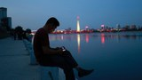 A man uses his phone as he sits along the Taedong river in Pyongyang, North Korea, September 12, 2018