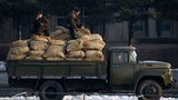 North Korean soldiers ride a truck loaded with grain in a file photo.