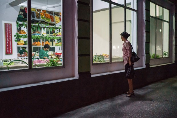 In a file photo, a woman stands outside a grocery store on a street in Pyongyang.
