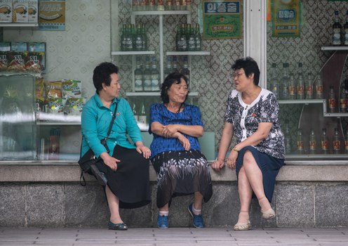 In a file photo, a group of women sit before a window display featuring food and drinks at a supermarket in Pyongyang, North Korea