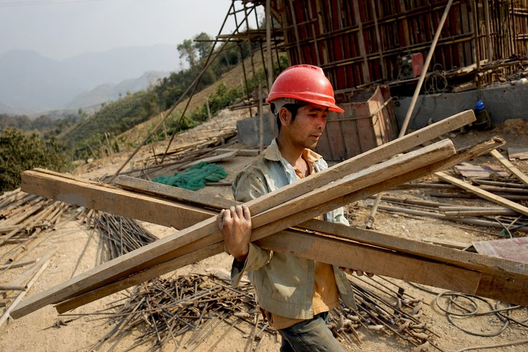 A Chinese worker carries materials for the first rail line linking China to Laos, a key part of Beijing's 'Belt and Road' project across the Mekong River, in Luang Prabang, Feb. 8, 2020. Credit: AFP