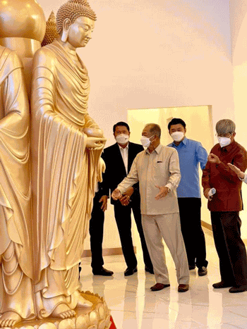 People admire a replica of the Mahayana-style, Chinese Buddha statue that the Wan Feng Shanghai Real Estate Company wants to build  in the That Luang Marsh Special Economic Zone in Vientiane, capital of Laos, in an undated photo. Credit: Vientiane's Special Economic Zone Promotion and Management Office