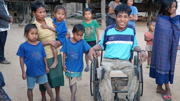 A disabled man sits in a wheelchair in his village in Ta-Oey district of southern Laos' Saravan province, where the toxic herbicide Agent Orange was sprayed, in an undated photo.