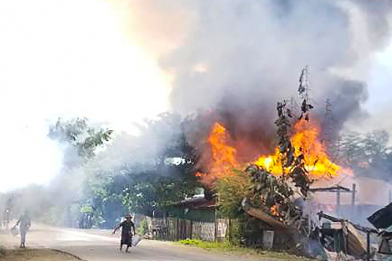 This handout received courtesy of an anonymous source on Sept. 18, 2021 shows people attempting to extinguish a fire as houses burn in Magway division, Sept. 10, 2021. AFP