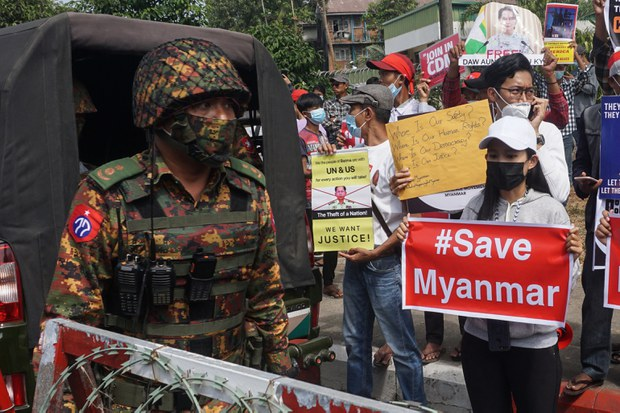 A soldier stands guard next to protesters holding signs during a demonstration against the military coup outside the Central Bank of Myanmar in Yangon, Feb. 15, 2021.