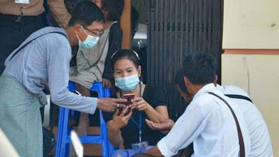 People access the internet using their mobile phones outside of an internet cafe in Naypyidaw, March 16, 2021.