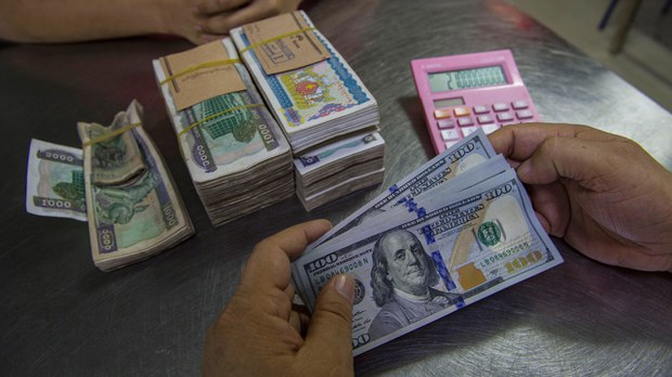 A money changer handles a transaction of US dollars and Myanmar kyats in Myanmar, in a file photo.