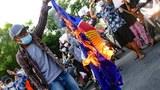 Anti-junta protesters burn the flag of the Association of Southeast Asian Nations (ASEAN) in Mandalay, Myanmar, June 5, 2021.