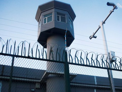 A guard watchtower rises along the perimeter fence of an internment camp in China's Xinjiang Uyghur Autonomous Region in a file photo.