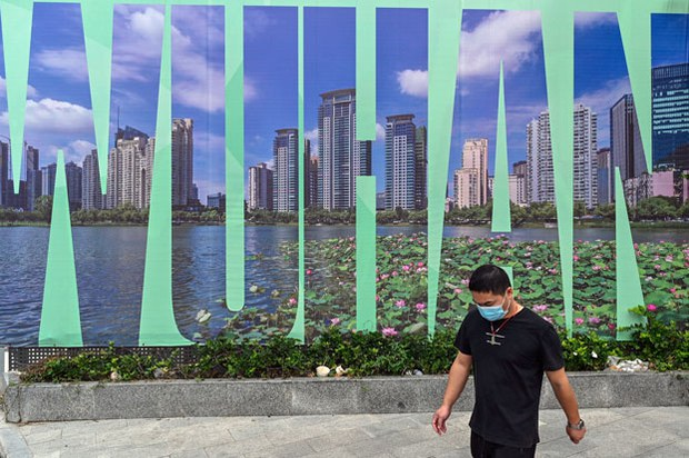 A man walks past a Wuhan sign in Wuhan, capital of central China's Hubei province, Sept. 28, 2020.