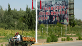 """Uyghur residents ride past a propaganda billboard showing Chinese President Xi  Jinping with ethnic minority children and the phase """"Sincerely thank the passionate care of the Party Central Committee with Comrade Xi Jinping as the core"""" in Peyziwat, Kashgar prefecture, northwestern China's Xinjiang region, Aug. 31, 2018."""
