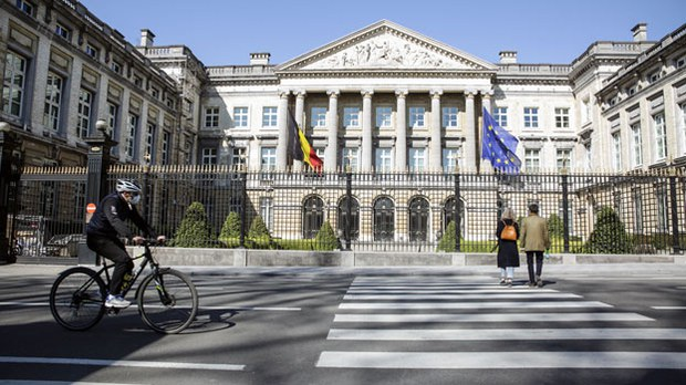 A cyclist rides by the Belgian Federal Parliament in Brussels, April 5, 2020.