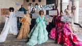 Models wear gowns made by designer Louise Xin while displaying signs and a banner during a digital fashion show in Stockholm, Sweden, August 2021.