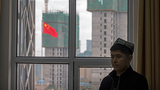 A Uyghur instructor stands near a window during a class at the Xinjiang Islamic Institute as a Chinese flag flies outside, in Urumqi, capital of northwestern China's Xinjiang region, April 22, 2021.