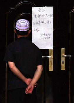 A Muslim man reads a sign attached to the entrance of a mosque telling worshipers to 'go home and pray there' in Urumqi, capital of northwestern China's Xinjiang Uyghur Autonomous Region, in a file photo. Credit: Reuters