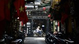 A man rides a motorbike past a hotel closed due to a surge in Covid-19 coronavirus cases in Hanoi, May 10, 2021.