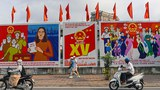 Vietnamese motorists pass signs about the upcoming National Assembly and People's Council elections, in Hanoi, May 19, 2021.