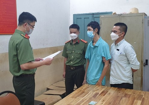 Vietnamese police read the arrest warrant for Doan Quang Vien (center) in this file photo.
